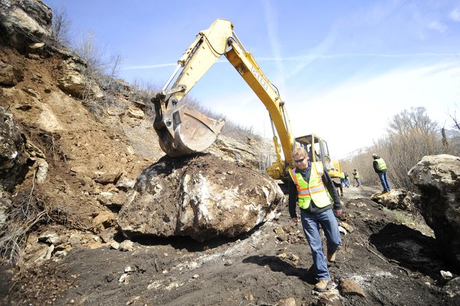 Steamboat Springs Department of Public Works engineer Ben Beall walks past a large rock Wednesday that was pulled down from alongside River Road.