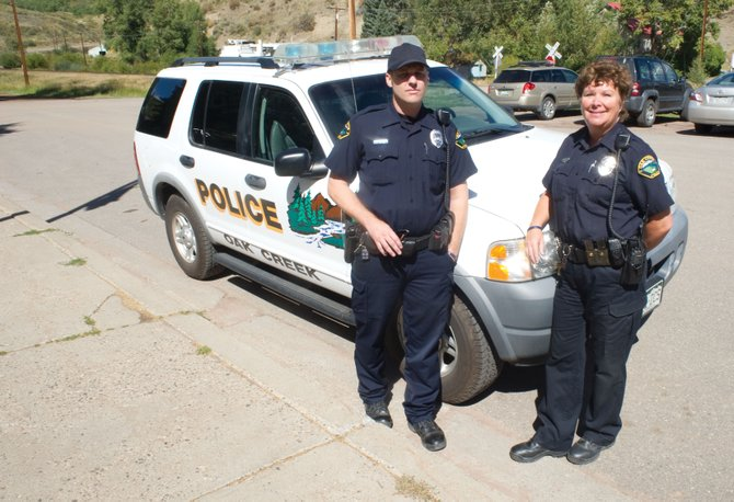 Oak Creek Police Department officers Lance Dunaway, left, and Eileen Rossi, a seasonal employee, stand by a squad car in front of the police department offices in downtown Oak Creek. Currently Oak Creek's lone officer, Dunaway has been having communication issues with Police Commissioner Chuck Wisecup.