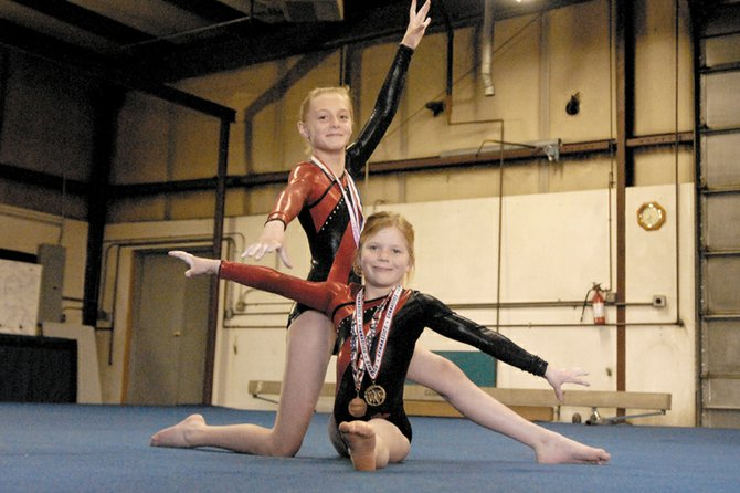 Trista Crittenden, front, and Gavyn Cox pose Tuesday in the gymnastics studio on Tucker Street. Crittenden, 8, and Cox, 11, competed in a Western Colorado Gymnastics meet Saturday in Montrose and took first and fifth, respectively. Both gymnasts will compete in the state meet June 24 and 25 in Denver.