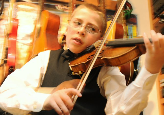 Jacob VanDerWerf's fingers dance across his violin Wednesday afternoon in his Steamboat Springs home. The 10-year-old musician won an award and was chosen to play at Merkin Concert Hall in New York City on April 15.