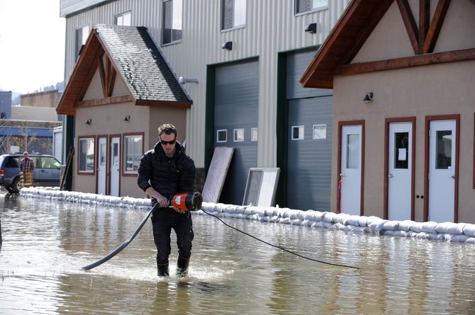 Rocky Mountain Remedies co-owner Kevin Fisher pumps flood water Thursday from around the building that houses one of his business's operations on 13th Street.
