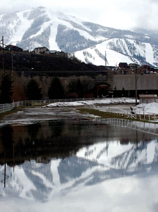 The snow-covered slopes of Mount Werner are reflected in the pools of water at Brent Romick Rodeo Arena in downtown Steamboat Springs on Monday. City and county officials are preparing for the possibility of significant flooding this spring.