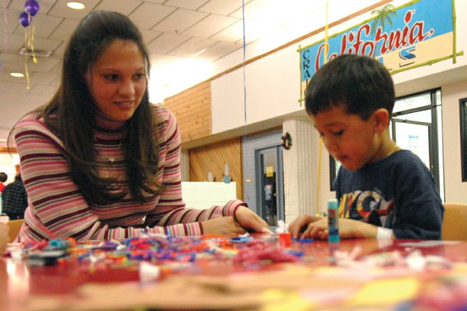 Derek Pedrosa and his mother, Annie, work on a butterfly magnet Saturday during the Moffat County Early Childhood Coalition's Celebrate Children Festival. The annual event allowed children to make crafts and play games. Organizers hoped to raise awareness of the importance of early education through the event.