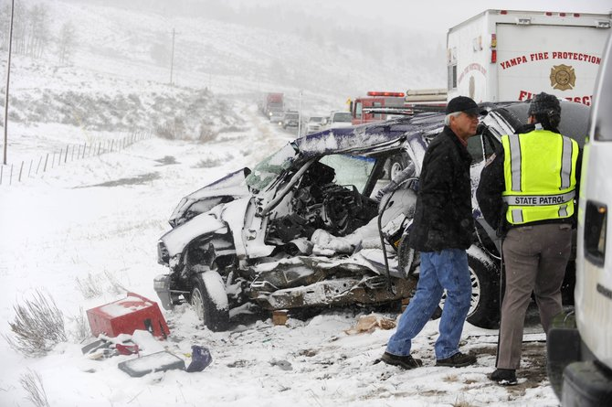 Colorado State Patrol Trooper Tonya Cowan, right, and Routt County Coroner Rob Ryg investigate an accident Friday on Colorado Highway 131 that killed 37-year-old Oak Creek resident Joseph Hehr.