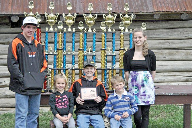 Xtreme Mountain Racing snowmobile riders, from left, Wesley Chapman, Bailey Wagner, A.J. Stoffle, Tallyn Wagner and Michelle Stoffle, stand with their year-end awards April 16 at Wyman Museum. While the sport requires traveling and is physically demanding, all five riders said they participate because they love to ride.