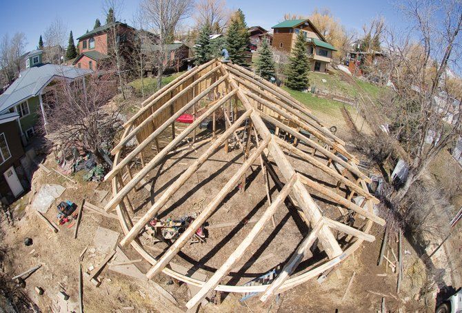 John Fielding puts the traditional pine bow on the top of a greenhouse that he is working on in the backyard of a private home in Old Town Steamboat Springs. He also is behind The Harvest Market, which is expected to open next week.