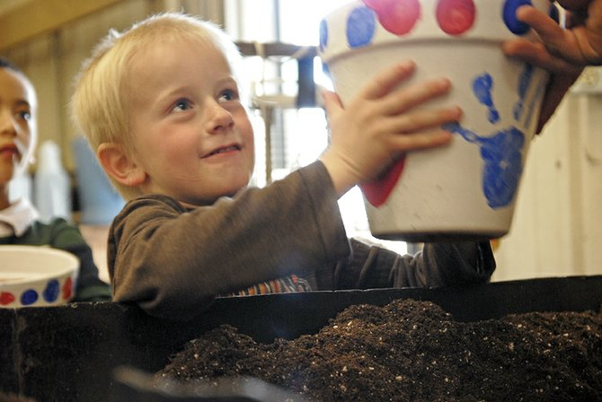 Sunset Elementary School kindergarten student Layne Tupa receives potting soil Thursday for his plant project at Moffat County High School's vocational agriculture building. Tupa and the rest of the Sunset student body were each given a terra cotta pot that they then painted. MCHS horticulture students provided the elementary school students with flowers and helped the younger children plant them throughout the day Thursday.