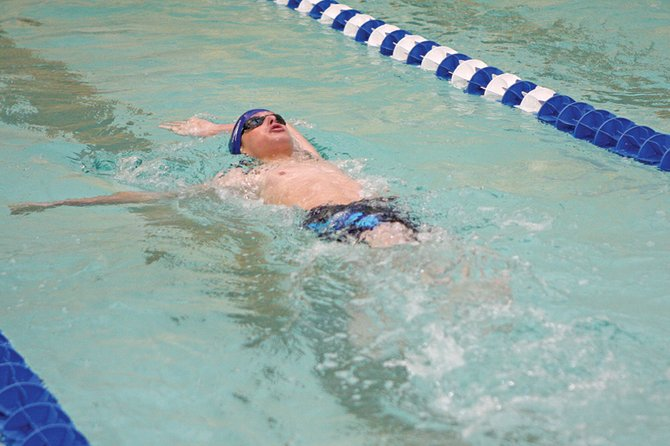Matt Hulstine, a Moffat County High School sophomore, swims the backstroke in the MCHS pool. MCHS boys varsity swimmers swam some of their best times this season April 30 in Grand Junction. The Bulldogs will swim in the only MCHS home meet this year at 3 p.m. Friday.