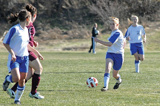 Kelsie Pomeroy passes the ball up field to teammate Kelly Ciesco, left, Wednesday at Loudy-Simpson Park. The Bulldogs couldn't overcome Palisade's two first-half goals and fell in the team's last home game of the season, 5-2.