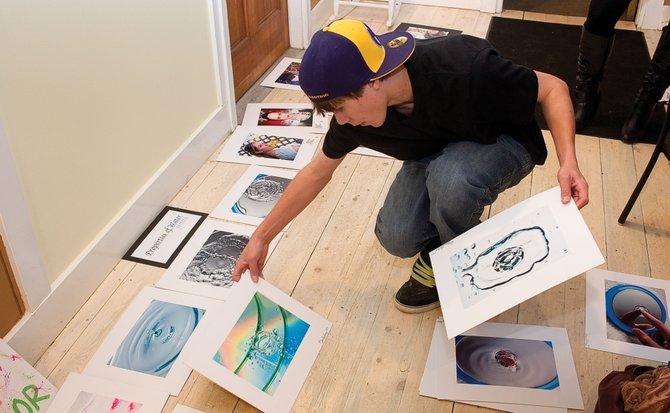 Steamboat Springs High School junior Sam Keating lays out his work at Chocolate Soup Pastry Cafe in downtown Steamboat Springs on Friday before hanging it on the walls. The show, which features several high school students, opened during First Friday Artwalk and will be held the rest of the month.