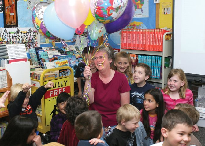 Cheryl Arnett, middle, a second-grade teacher at Sunset Elementary School, smiles after being awarded the 2010-2011 Craig Daily Press Teacher of the Year trophy and balloons on Friday morning in her classroom. The Daily Press' Editorial Board selected Arnett from 100 nominations for 33 area teachers.