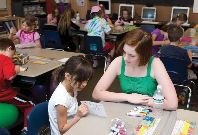 Sixth-grader Makayla Woods visits with second-grader Kaedynce Kaleikiini at Soda Creek Elementary School on Tuesday as part of Global Youth Service Day.