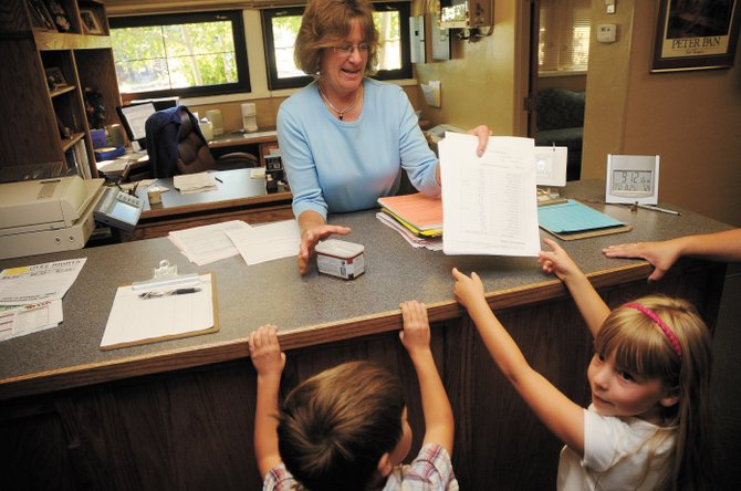 Kindergartners Abby Voorhis, right, and Isaac Iacovetto hand in paperwork from their class to Cheryl Sullivan in August 2009. Abby, now a first-grader, was diagnosed with leukemia in April.