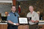 Craig Police Department Officer Ryan Fritz accepts the Craig Police Department's Life Saving Medal from Police Chief Walt Vanatta at Tuesday's Craig City Council meeting. Fritz helped three Moffat County Sheriff's Office deputies save the life of an inmate who had a heart attack. Fritz said any other officer in the situation would have done the same thing.