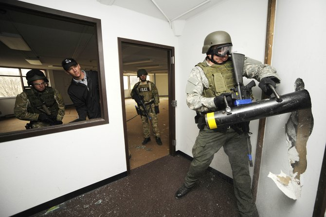 Routt County Sheriff's Office deputy Jake Carlson breaks through a wall Thursday during special weapons and tactics training at Colorado Mountain College's Monson Hall.