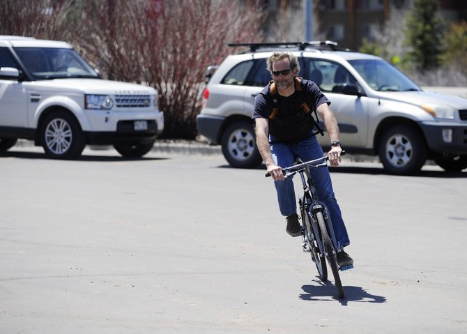 Steamboat Springs City Council member Scott Myller bikes to Friday's meeting to discuss the economic impacts of cycling and how local businesses could profit.