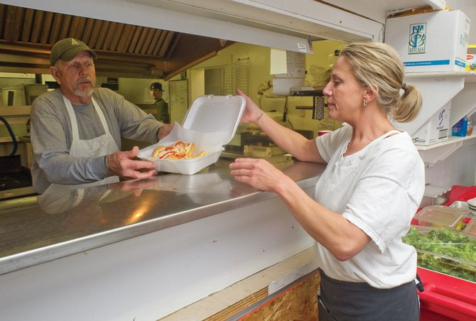 Wolf Mountain Pizza employee Lori Fournier takes a to-go meal from Charlie Epp on Thursday in the business in downtown Hayden.