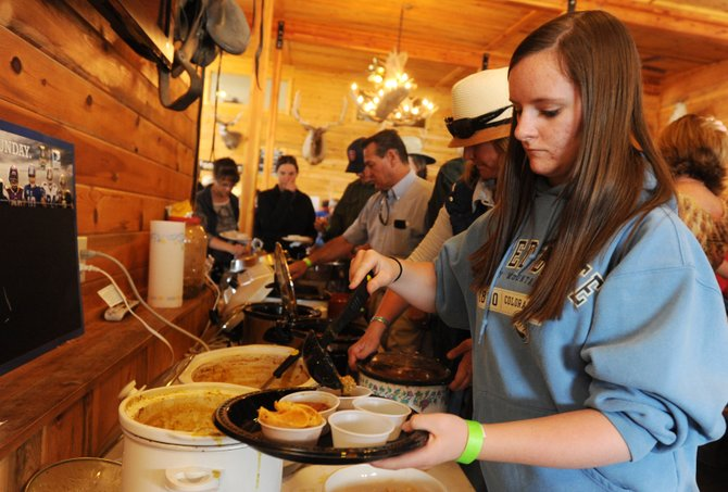 Mary White scoops a cup of chili onto her plate Sunday at the North Routt Chili Cook Off at Steamboat Lake Outfitters. 
