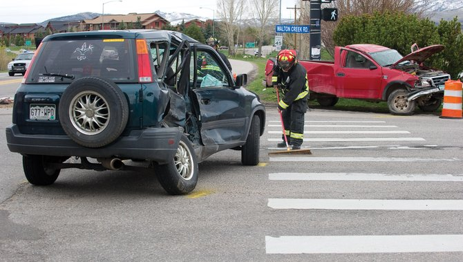 Steamboat Springs Fire Rescue's Travis Wilkinson cleans up after a two-car crash on U.S. Highway 40 and Walton Creek Road on Monday afternoon. Two men were taken to the Yampa Valley Medical Center after the collision.