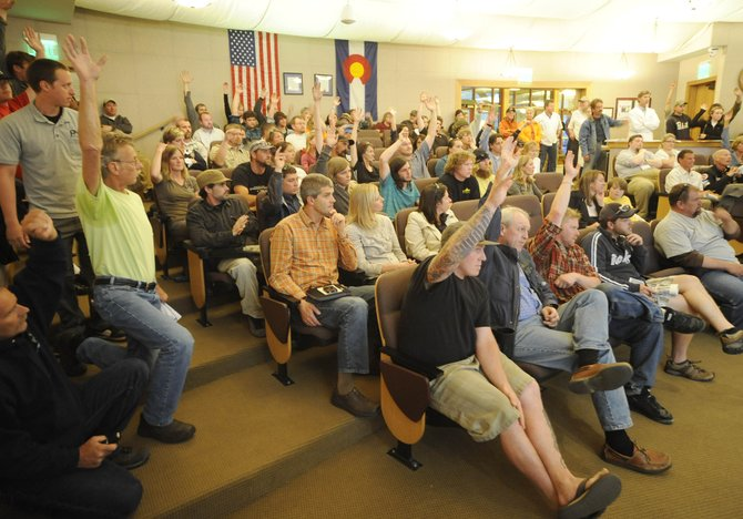 People raise their hands to show their support for medical marijuana dispensaries in Steamboat Springs during Tuesday night's Steamboat Springs City Council meeting. Council members voted, 4-3, against a ban on medical marijuana dispensaries and unanimously voted to send the question to voters in November.