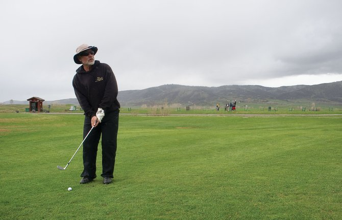 Steamboat Springs resident Mike Baumann lines up a shot while hitting balls at the practice facility at Haymaker Golf Course in Steamboat Springs. The practice facility and driving range opened last week, and the course is expected to open Friday.