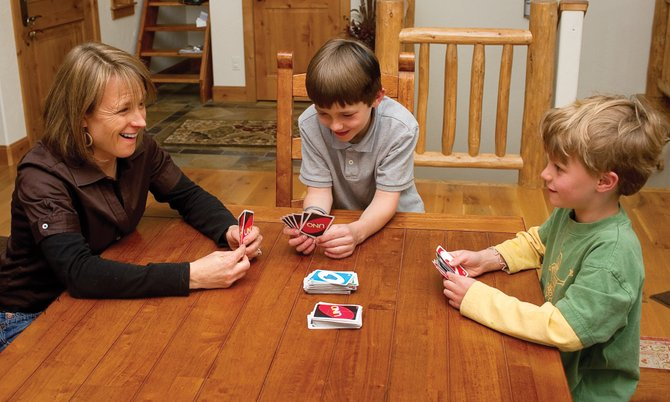 "Karin Kagan plays ""Uno"" with her sons Kyle, middle, and Colin at their home on Copper Rose Court, off Fish Creek Falls Road. New census data show small shifts in household demographics but overall stability in local family trends during the past decade, indicating the family-friendly community feeling that's central to life in Steamboat for many. ""We always said if we could make it work, we'd stay here because it's such a great place to raise a family,"" Karin said about conversations with her husband, Josh Kagan."