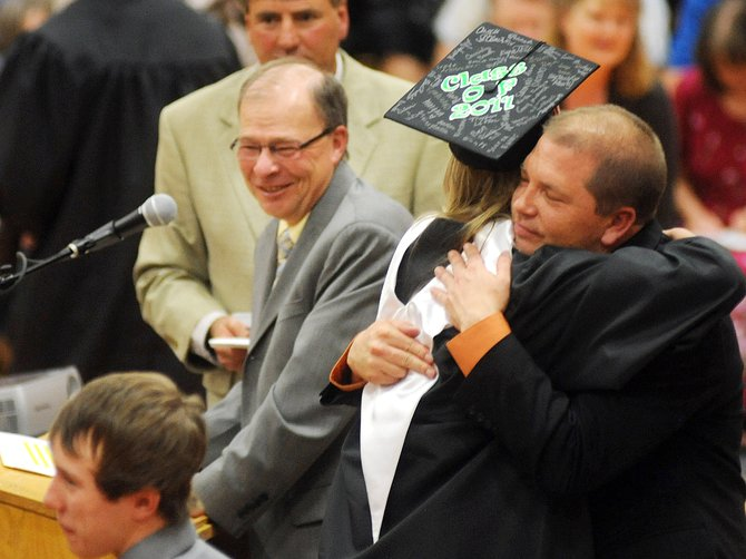 Hayden Secondary Schools principal Troy Zabel hugs graduating senior Kalina McFadden on Sunday at the school. Sunday marked the end of school in Hayden for 38 seniors, and also for Zabel, who resigned his position earlier this year.