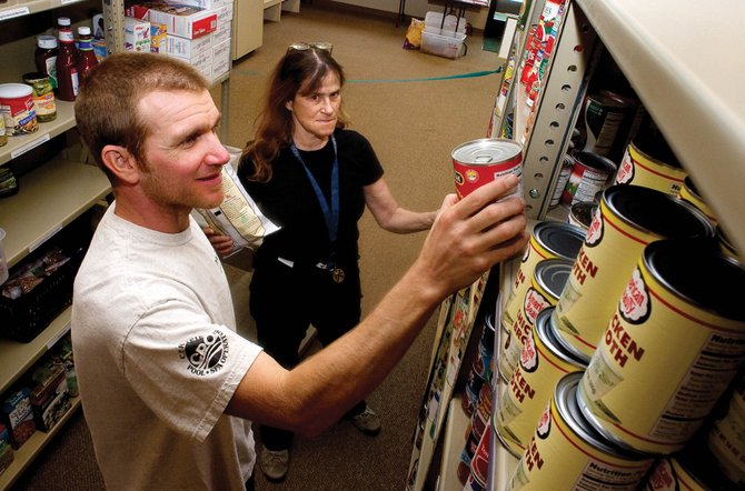 LIFT-UP of Routt County volunteers Danny Tebbenkamp and Candace Noriega stock the selves of the food bank Monday afternoon. LIFT-UP is marking its 15th year serving Steamboat Springs.