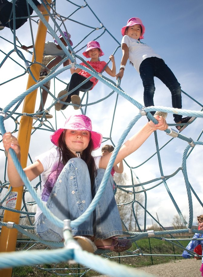 Christian Heritage School second-grader Katelynn Duckels, middle, plays with Piper Eivins, right, and Aliyah Reimer on the playground of the school Monday afternoon.