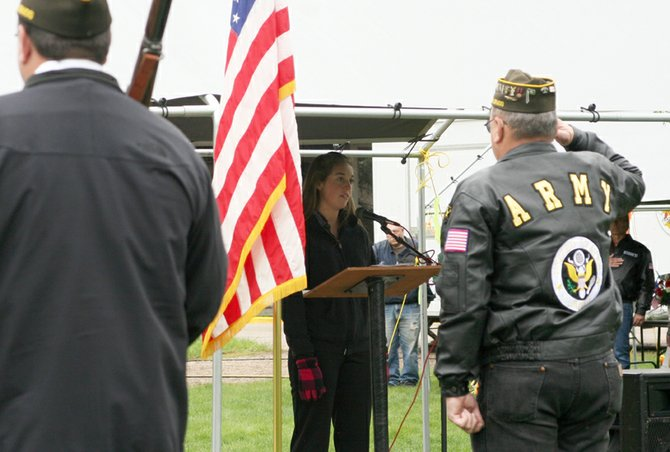 The Veterans of Foreign Wars Post 4265 color guard stands at attention as Karen Bolton, 17, sings the national anthem Saturday during the annual Hometown Heroes Community Picnic at Craig City Park.
