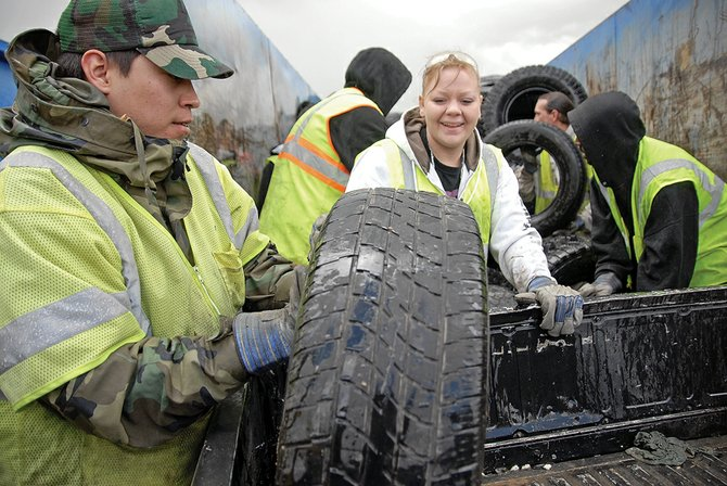 Ike Reedy, left, of Hayden, and Nikki Granados, of Craig, dispose of used tires Saturday at Craig City Park. The two were among several volunteers at Craig Clean-Up Days. Over the weekend, city employees helped residents dispose of used tires, appliances and other unwanted items.