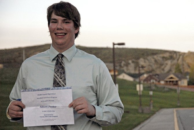 Moffat County High School junior Adam Foster stands Tuesday outside the school with a $1,000 scholarship to the school of his choosing. Two $1,000 scholarships were presented by the MCHS Student Council Seatbelt Awareness Committee at the school auditorium during Academic Awards Night. MCHS senior Emily Miller also won, but was not present. The students won the scholarships for wearing seatbelts.