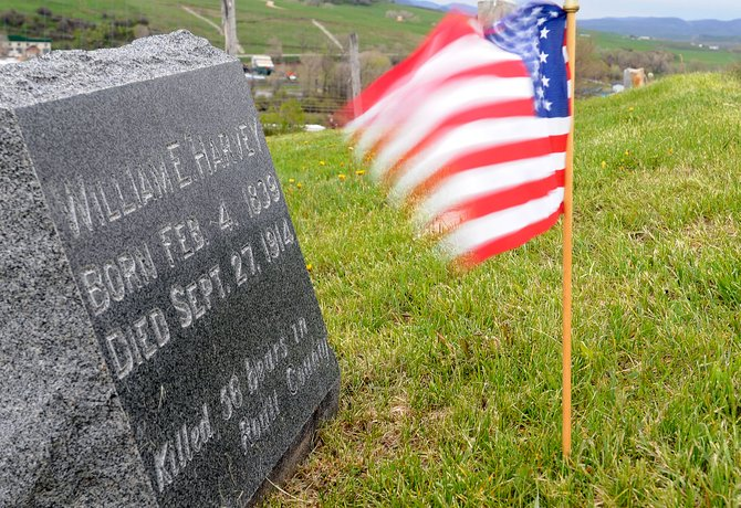 The Stars and Stripes whip in the wind in front of the grave of William E. Harvey, a Civil War veteran buried in Steamboat Springs Cemetery. Kentucky librarians say evidence indicates William E. Harvey was not a Confederate soldier and likely fought for the Union.