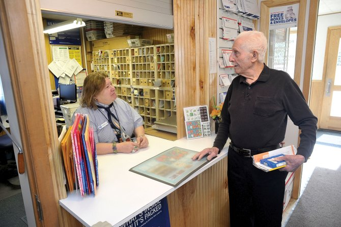 "Mariea ""CC"" Connor, the postmaster officer-in-charge of the Phippsburg Post Office, visits with patron Rocco Stefano on Thursday after he picks up his mail. The post office, which is a favorite gathering place for many longtime residents, is in jeopardy of closing down."