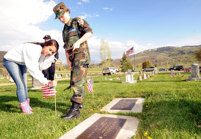 Reina Salky, 14, right, and Michaela Graham place a flag in front of the grave of World War II veteran Sylvia Boggs.