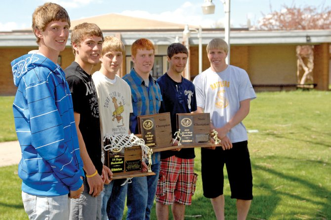 From left, Miles Englehart, Rex Stanley, Grayson Lee, Daniel Wille, Conner Lee and Sean Rietveld stand with their football, basketball, and track and field state trophies Wednesday outside the Little Snake River Valley School in Baggs, Wyo. While the six athletes, along with Chance Englehart, not pictured, competed on all three state championship teams, they also maintained high grade point averages in the classroom and helped bring the Baggs community together.
