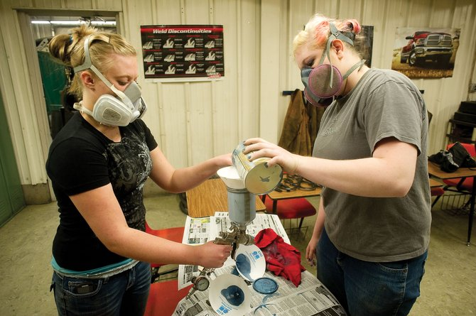 Beth Leck, left, and Kelsea DeBowes mix paint at the Babson-Carpenter Career and Technical Education Center in Hayden during their auto body class last week.