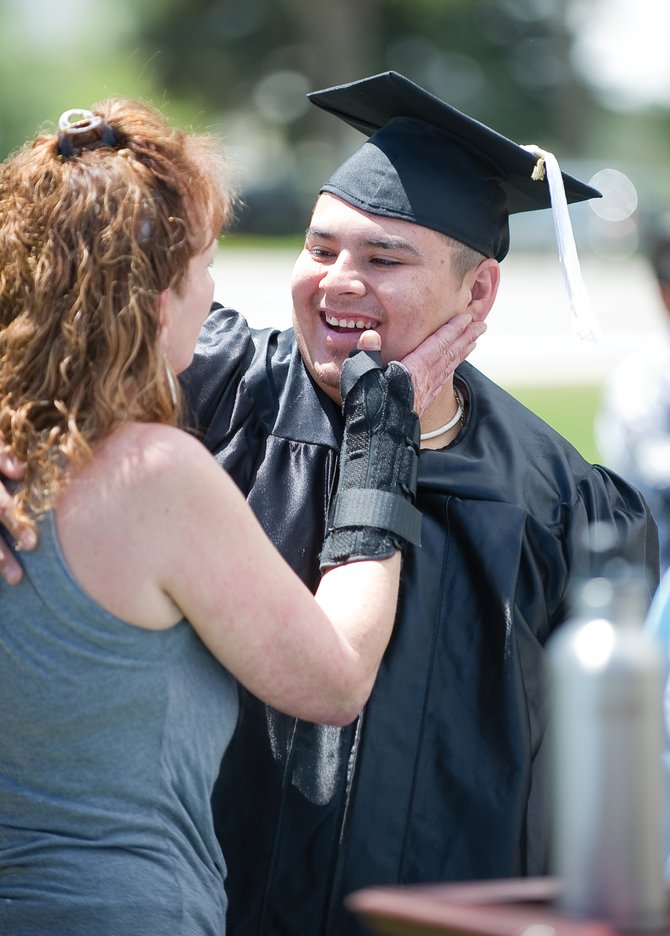 Danilo Medina is congratulated by close friend Jackie Thomas during the Yampa Valley High School's Graduation Friday on the lawn of the George P. Sauer Human Services Center. Medina said Thomas, who he works with at the Cantina Mexican Restaurant, is like a mother to him.