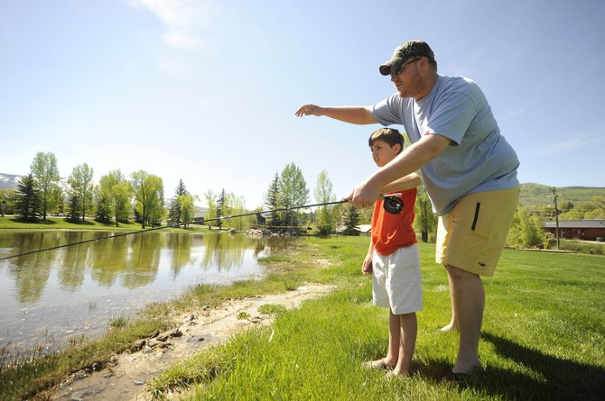 Tim Kirkpatrick, co-owner of Steamboat Flyfisher, works with 8-year-old Finn Ridings during a clinic Saturday at West Lincoln Park. A prolonged runnoff likely will have an effect on numerous local business such a Steamboat Flyfisher.