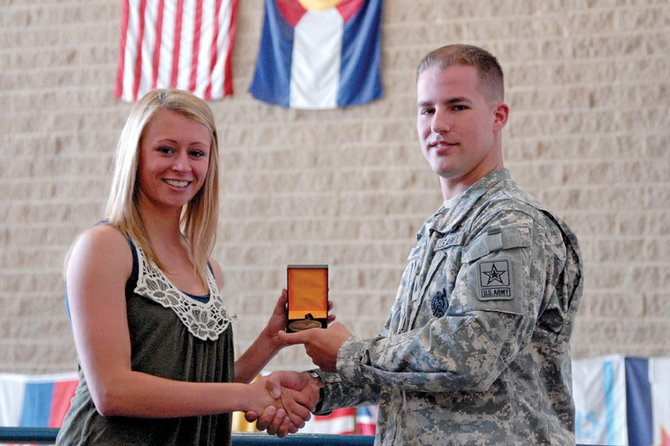 Lauren Roberts receives the Army Scholar Athlete award Monday from Sgt. Eric Borror at Moffat County High School. Roberts graduated with a 4.0 grade point average while lettering in track and field for four years and volleyball and basketball for three years.