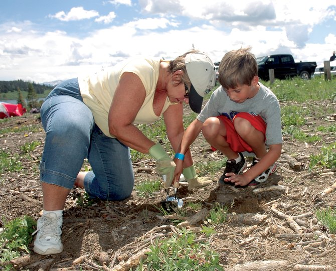 Patti Rackstein and her grandson Colton Mays plant a lodgepole pine seedling at Steamboat Lake State Park at last year's ReTree Colorado. Registration for this year's event begins at 8:30 a.m. Saturday.