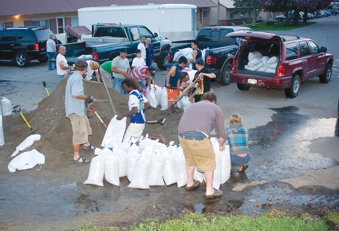 Residents of Dream Island Mobile Home Park were busy filling sandbags Monday evening as the Yampa River began to flood streets in the neighborhood.