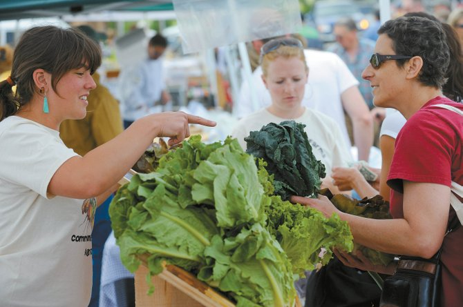 Steamboat Springs resident Julie Hagenbuch picks up some greens from fellow Steamboat resident Sarah Braat, who was working at the Grant Family Farms booth, in June 2009 at Mainstreet Farmers Market.