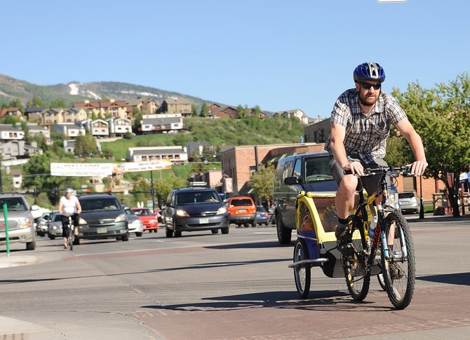 Matt Hall rides down a busy Lincoln Avenue in downtown Steamboat Springs on Friday afternoon, pulling his 3 1/2-year-old son, Will.