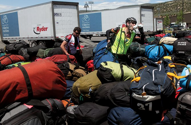 Chuck Matthys, right, takes a swig of water after locating his baggage as Thaseus Eby keeps searching for his in the massive pile brought in on trucks for the Ride the Rockies participants Monday at Battle Mountain High School in Edwards. The multi-day bike ride through Colorado has riders camping overnight at Freedom park before continuing to Steamboat Springs on Tuesday.