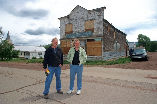 Wendy Moreau, Yampa resident and curator of Yampa Historical Museum, and Jeff Drust, Friends of Crossan's president, stand in front of the Crossan's Market building in Yampa. The Friends of Crossan's hope to restore the historic building in downtown and preserve part of the town's rich history in the process.