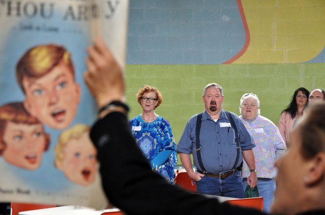 """Charlene Kirby, from left, and Drew and Doris Schrupp sing """"How Great Thou Art"""" on Sunday at the annual Father's Day picnic in McCoy. McCoy community members have sung the song at the start of their picnic since the gathering of the community first started in 1968."""