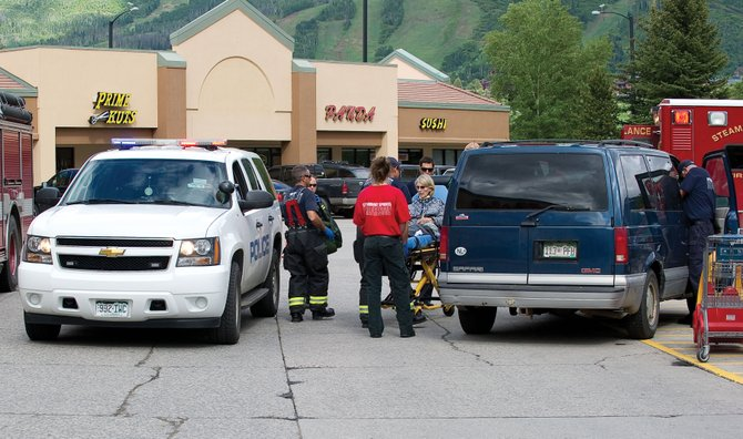 A women is taken from her vehicle in the City Market parking lot after the van she was in struck a pedestrian Monday afternoon. 