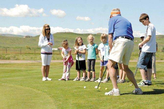 Ken Harjes, the Moffat County High School boys golf coach, and MCHS golfer Caitlin Harjes, left, show youth golfers how to chip Tuesday during the Yampa Valley Golf Course's junior golf clinic.