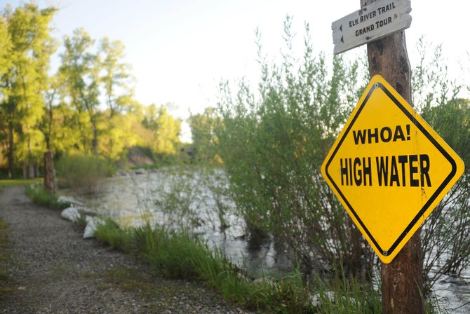The Elk River laps earlier this week at its banks along Marabou Ranch beneath a sign warning of the high water. Area rivers and creeks are again expected to rise this weekend.